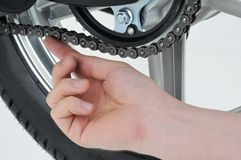 Chain tension. Motorcycle mechanic checking the tension on a chain Royalty Free Stock Photo