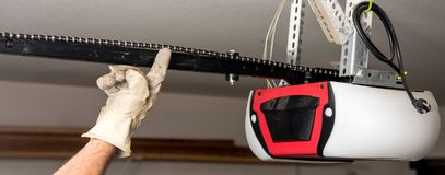 Testing the chain tension on a garage door opener Royalty Free Stock Photo