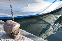 Chain tied on a bollard. Mooring rope wrapped around the cleat on sea background. Metal capstan in harbor for the mooring of yacht Royalty Free Stock Photography