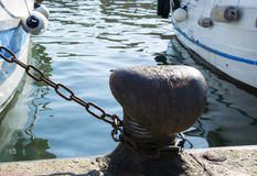 Chain tied on a bollard. Mooring rope wrapped around the cleat on sea background. Metal capstan in harbor for the mooring of yacht Royalty Free Stock Photos