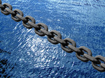 Chain on water. Black chain on a tall ship royalty free stock images