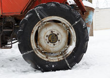 Chain at the wheel of the tractor on snow surface Stock Photos
