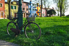 Chained bicycle in green grass in front of colorful houses in Burano, Italy. Old black city bicycle with basket chained to a pole in grass in front of colorful stock photos
