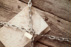 Chained book on wooden background Stock Photography