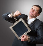 Chained businessman with a board Stock Images