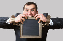 Chained businessman with a board Royalty Free Stock Images