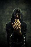 Chained cultist. Portrait of miserable chained young man in hood Royalty Free Stock Photos