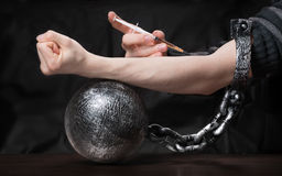Chained by drugs. Metaphor for being a slave of drug addiction Royalty Free Stock Photography
