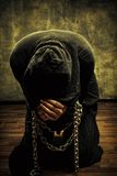 Chained fanatic. Miserable monk praying on his knees in dark room Stock Photos