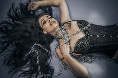 Chained, Fashion shoot of young brunette woman in fetish dress, Royalty Free Stock Image