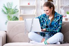 Chained female student with laptop sitting on the sofa Royalty Free Stock Photography