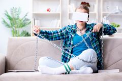 The chained female student with virtual glasses sitting on the sofa. Chained female student with virtual glasses sitting on the sofa Stock Image