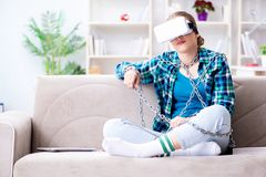 The chained female student with virtual glasses sitting on the sofa. Chained female student with virtual glasses sitting on the sofa Stock Photos