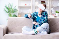 The chained female student with virtual glasses sitting on the sofa. Chained female student with virtual glasses sitting on the sofa Royalty Free Stock Image