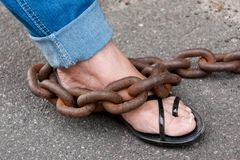 Chained Foot. Woman foot chained with very thick and rusty chain Royalty Free Stock Photos