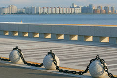 Chained granit. Fragment of quay on a background of slightly blured new buildings and gulf Stock Image
