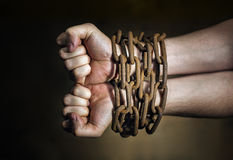 Chained. Hands of a man with a rusty chain around the wrists Stock Image