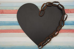 Chained heart. On the wooden colored plank Stock Photo