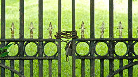 Chained Iron Gate. Chains and locks hold a rusting iron gate closed royalty free stock photo