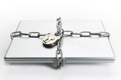 Chained laptop. Closed laptop computer with chain wrapped around it and padlocked stock photo