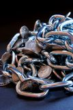 Chained money. Image of a pile of coins in chains, conceptual security or access to money issues stock image