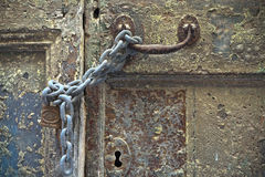 Chained and padlocked door. Chained and padlocked weathered painted door royalty free stock photos