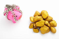 Chained piggy bank and gold Stock Images
