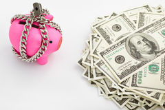 Chained piggy bank and pile of dollars Royalty Free Stock Photo