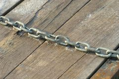 Chained Planks. A chain is draped across weathered planks of wood Royalty Free Stock Images
