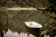chained rowing boat floats on a lake stock photo