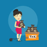 Chained taxpayer with bags full of taxes. Stock Photo