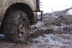 Chained up tire on a very muddy road. Royalty Free Stock Images