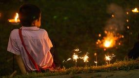 Chaing Mai,泰国, 2015年4月15日-男孩坐并且演奏烟花 免版税库存照片