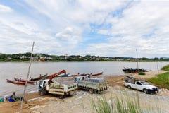 CHAING RAI, ТАИЛАНД - 22-ОЕ ИЮНЯ 2015: продукт работника нагружая к пропуску Меконгу Таиланду маленькой лодки для того чтобы гран стоковое фото rf