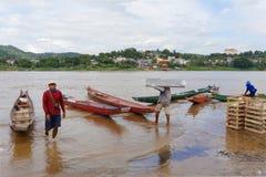 CHAING RAI, ТАИЛАНД - 22-ОЕ ИЮНЯ 2015: продукт работника нагружая к пропуску Меконгу Таиланду маленькой лодки для того чтобы гран стоковая фотография rf