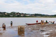 CHAING RAI, ТАИЛАНД - 22-ОЕ ИЮНЯ 2015: продукт работника нагружая к пропуску Меконгу Таиланду маленькой лодки для того чтобы гран стоковые изображения