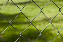 Chainlink. Closeup of chainlink fence with blurred grass background Stock Photos