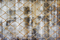 Chainlink fence against wall background Royalty Free Stock Photo