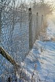 Chainlink fence in winter. And frozen grass Stock Photos