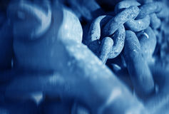 Chains. Rusty metal chains at the dock , blue toned conceptual photo with soft focus stock photos