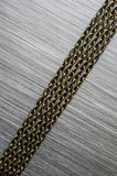 Chains on brushed metal background Royalty Free Stock Photos