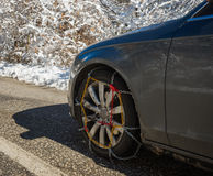 Chains on car weels in snowy mountains during winter Stock Image
