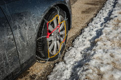 Chains on car weels in snowy mountains during winter Royalty Free Stock Photography