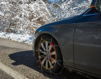 Chains on car weels in snowy mountains during winter Stock Photo