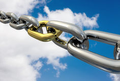 Chains Golden Link, isolated. Row of chrome chains with a golden link on a blue sky, isolated Royalty Free Stock Photography