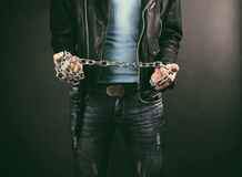 Chains in hands. Of young man on a gray background royalty free stock photo