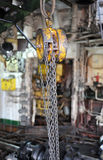 Chains hanging from a hoist in workshop. Close up of chains hanging from a hoist in the engine roon on the ship Royalty Free Stock Photo