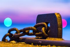Rusty chain rattling in Landskrona harbor. Chains in the harbor. The harbur inlet guide lights in bokeh Royalty Free Stock Images