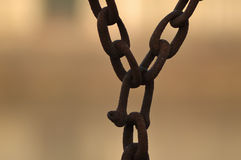 Chains. Old iron chains hanging on an orange background Royalty Free Stock Photography
