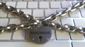 Chains and padlock with MALWARE text on the computer keyboard. Conceptual 3D animation